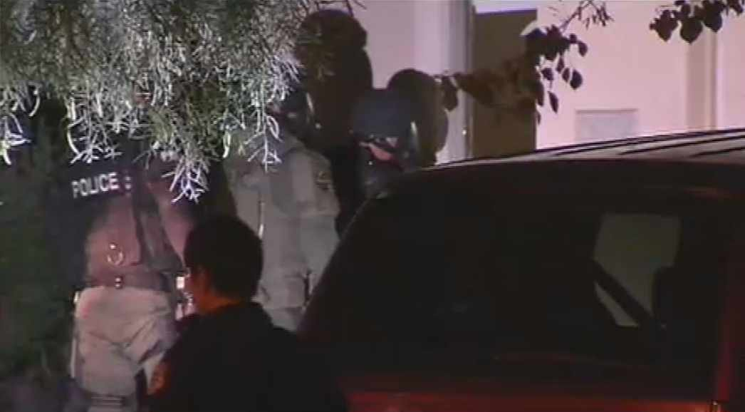 El Mirage police and Surprise SWAT members make their way into a home before taking a man barricaded in a bedroom into custody. (Source: CBS 5 News)