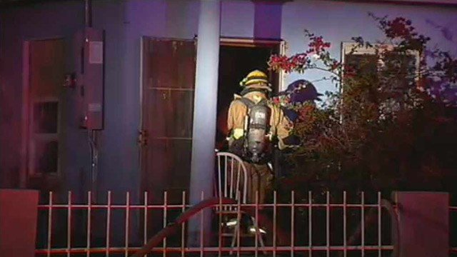 A Phoenix firefighter enters the front part of two residences that caught fire Thursday night. (Source: CBS 5 News)