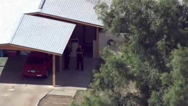 Phoenix police stand at a house where a homeowner shot and wounded a burglary suspect Tuesday morning. (Source: CBS 5 News)