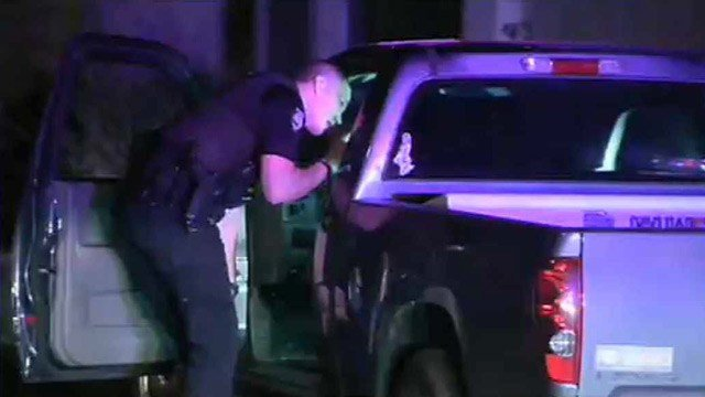 A Peoria police officer gathers evidence from a pickup truck that was carjacked Tuesday night. (Source: CBS 5 News)