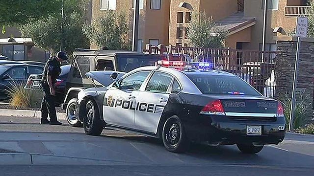 Tempe police check vehicles at an apartment complex after a reported home invasion in which weapons might have been stolen Tuesday morning. (Source: CBS 5 News)