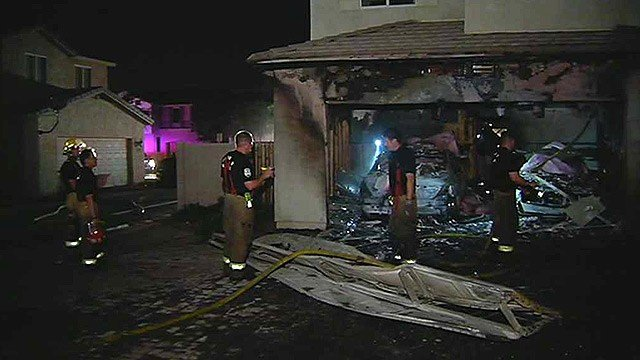 A garage fire destroyed the two cars inside, but firefighters were able to limit the damage to the attached house. (Source: CBS 5 News)