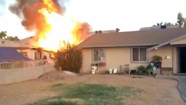 Neighbor John Tate grabbed his cell phone and began recording the early moments of this house fire as Phoenix firefighters arrived. (Source: John Tate)