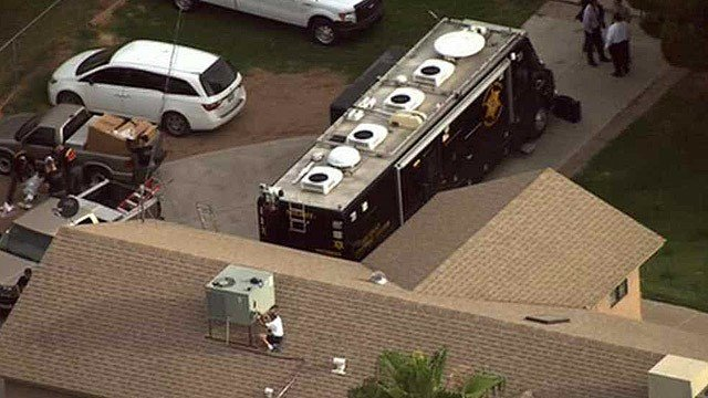 Forensic experts check the air conditioning system at a home in Gilbert where 20 dogs died last week. (Source: CBS 5 News)