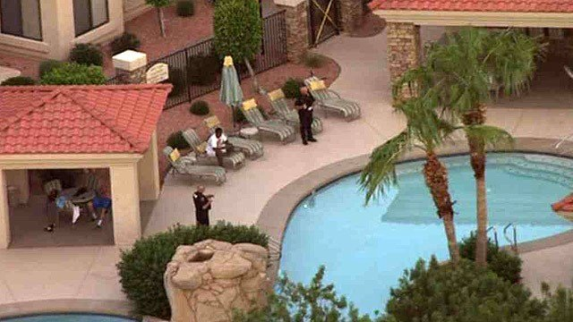 Glendale police stand near a pool after a 16-year-old boy was pulled from the water and taken to a hospital, where he died Monday morning. (Source: CBS 5 News)